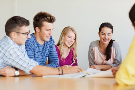 college building: education, school, architecture and people concept - group of smiling students with blueprint meeting indoors Stock Photo