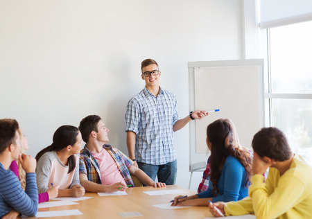 education, teamwork and people concept - smiling students with white board sitting an table indoors Standard-Bild