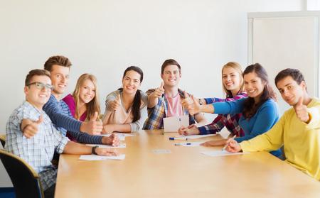 교육, 팀워크, 제스처와 사람들이 개념 - 논문 엄지 손가락을 보여주는 테이블에 앉아 웃는 학생들 스톡 콘텐츠