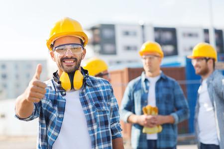 비즈니스, 건물, 팀웍, 제스처 및 사람들이 개념 - 야외에서 엄지 손가락을 보여주는 hardhats에서 웃는 빌더의 그룹