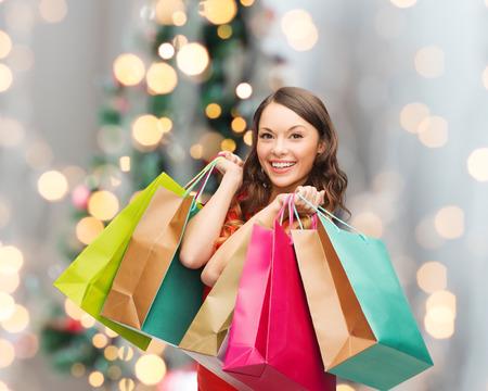 verkoop, geschenken, vakanties en mensen concept - lachende vrouw met kleurrijke boodschappentassen over een woonkamer en kerst boom achtergrond