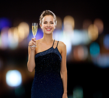 party, drinks, holidays, people and celebration concept - smiling woman in evening dress with glass of sparkling wine over night lights background photo