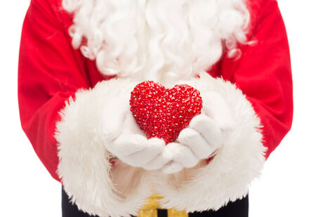 nicolas: christmas, holidays, love, charity and people concept - close up of santa claus with heart shape decoration