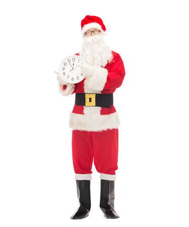 twelve month old: christmas, holidays and people concept - man in costume of santa claus with clock showing twelve pointing finger