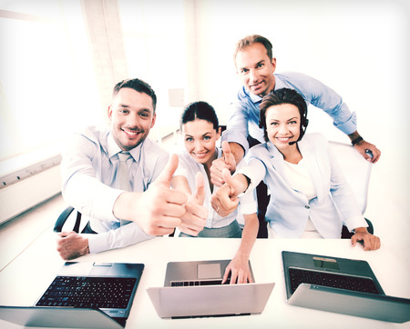 thumbs up group: business concept - group of office workers showing thumbs up in call center
