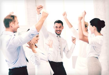 gente bailando: imagen del equipo de negocios feliz celebrando la victoria en la oficina Foto de archivo