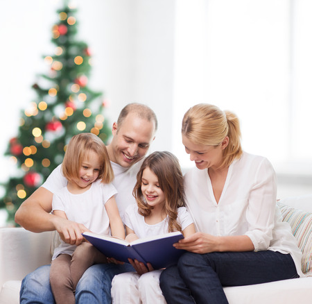 family, childhood, holidays and people - smiling mother, father and little girls reading book over living room and christmas tree background photo