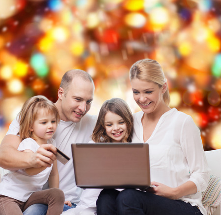 family, holidays, shopping, technology and people - happy family with laptop computer and credit card over red lights background photo