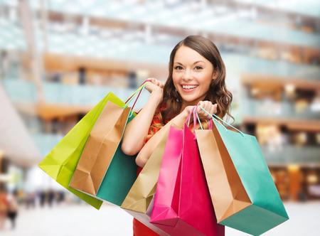 판매, 선물, 휴일 및 사람들 개념 - 쇼핑 센터 배경 위에 다채로운 가방과 함께 웃는 여자 스톡 콘텐츠 - 32612128