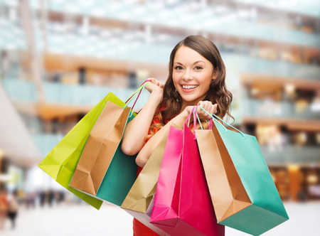sale, gifts, holidays and people concept - smiling woman with colorful bags over shopping center background