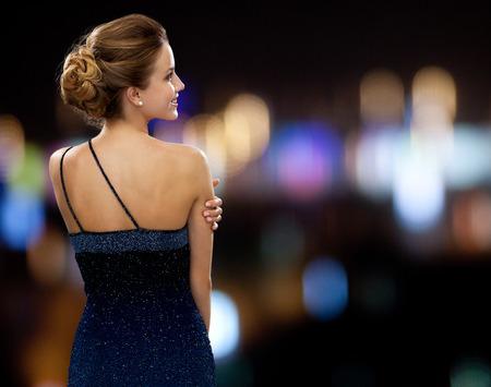 人、休日とグラマーのコンセプト - 夜ライト背景にイブニング ドレスの女性を笑顔 写真素材