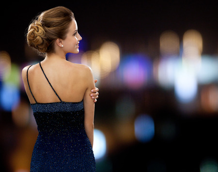 luxury lifestyle: people, holidays and glamour concept - smiling woman in evening dress over night lights background