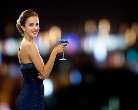 party, drinks, holidays, people and celebration concept - smiling woman in evening dress holding cocktail over night lights background
