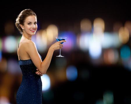 partij, dranken, vakantie, mensen en vieringsconcept - glimlachende vrouw in de cocktail van de avondjurkholding over de achtergrond van nachtlichten Stockfoto