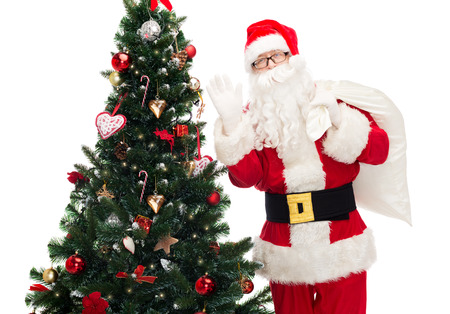 christmas, holidays and people concept - man in costume of santa claus with bag and christmas tree waving hand photo