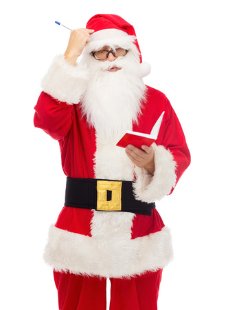christmas, holidays and people concept - man in costume of santa claus with notepad and pen photo