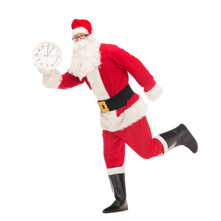 twelve month old: christmas, holidays and people concept - man in costume of santa claus running with clock showing twelve Stock Photo