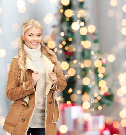 christmas shopping: winter holidays, fashion and people concept - smiling young woman in winter clothes over christmas tree lights background Stock Photo
