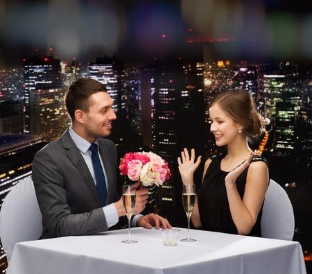 aniversario: restaurante, la pareja y el concepto de vacaciones - hombre sonriente que da el ramo de flores a la mujer en el restaurante