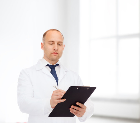 medicine, profession, workplace and healthcare concept - serious male doctor with clipboard writing prescription over white room background photo