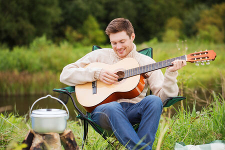 adventure, travel, tourism and people concept - smiling man with guitar and cooking food on bonfire in camping photo