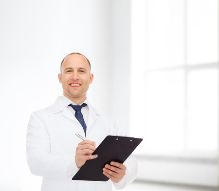 medicine, profession, workplace and healthcare concept - smiling male doctor with clipboard writing prescription over white room background photo