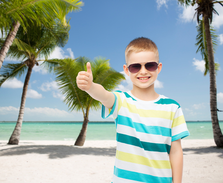 childhood, travel, summer vacation, gesture and people concept - smiling little boy wearing sunglasses over beach background photo