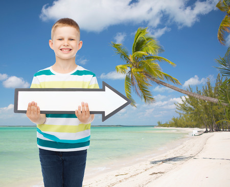 directive: advertising, direction, summer, travel and childhood concept - smiling little boy with white blank arrow over tropical beach background Stock Photo