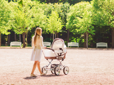 family, child and parenthood concept - happy mother walking with baby stroller in park from back Stock Photo