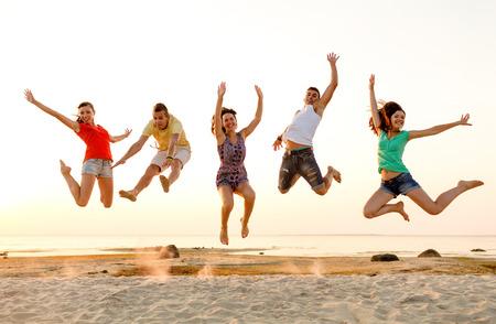 amistad: amistad, las vacaciones de verano, las vacaciones, el partido y la gente concepto - grupo de amigos sonrientes bailando y saltando en la playa Foto de archivo