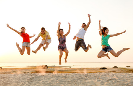friendship: friendship, summer vacation, holidays, party and people concept - group of smiling friends dancing and jumping on beach Stock Photo