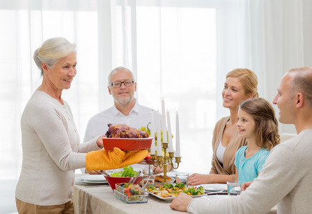 three generation: family, holidays, generation and people concept - smiling family having dinner at home