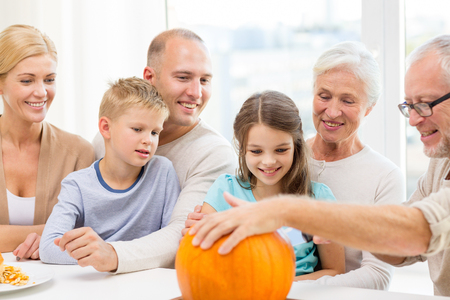 kids having fun: family, happiness, generation, holidays and people concept - happy family making halloween pumpkins at home