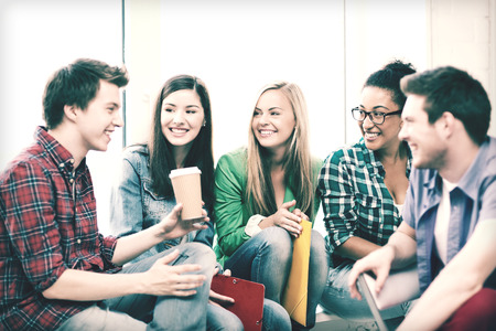 happy teens: education concept - students communicating and laughing at school