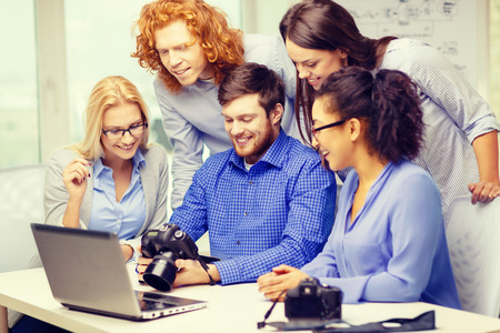 business, office and startup concept - smiling creative team with laptop computer and photocameras working in office photo
