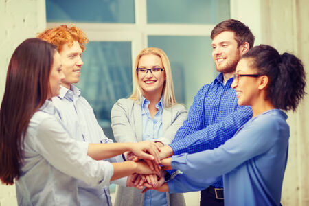 developers: business, office, gesture and startup concept - smiling creative team with hands on top of each other sitting in office Stock Photo