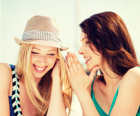 nice looking: friendship, happiness and people concept - two smiling girls whispering gossip