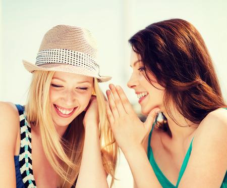 amigos hablando: la amistad, la felicidad y la gente concepto - dos niñas sonrientes que susurran chisme