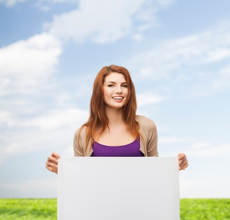 advertising, education and people concept - smiling teenage girl with blank white board over blue sky and grass background photo