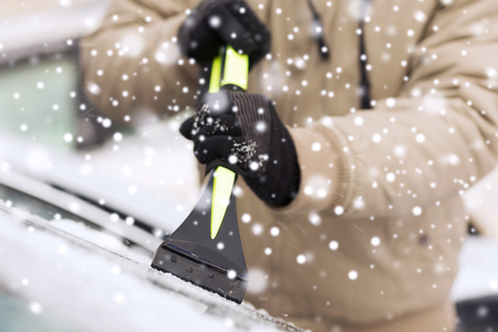 closeup of man cleaning snow from car windshield with brush Stok Fotoğraf