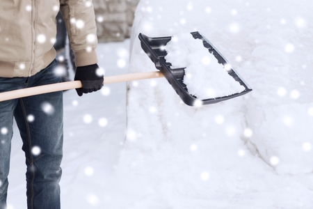 transportation, winter, people and vehicle concept - closeup of man digging snow with shovel near car photo