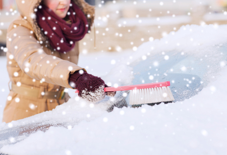 closeup of woman cleaning snow from car windshield with brush photo