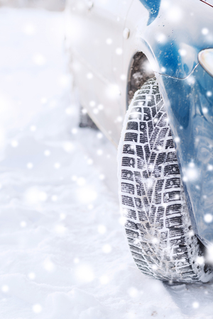 transportation, winter and vehicle concept - closeup of car wheel photo