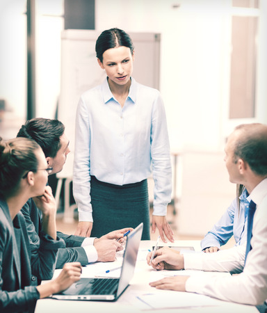 female boss: business, technology and office concept - strict female boss talking to business team