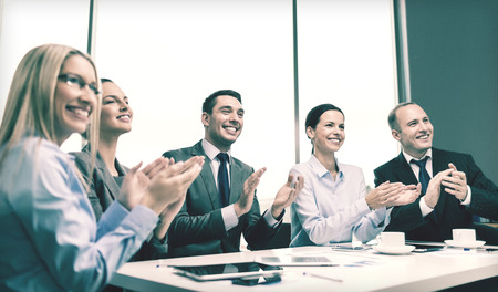 people clapping: happy business team with laptop computers, documents and coffee clapping hand