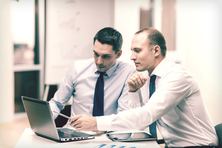 two: two businessmen with laptop, tablet pc computer and papers having discussion in office