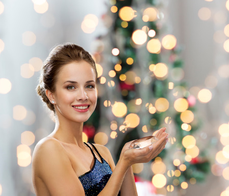 huge christmas tree: smiling woman in evening dress with diamond over christmas tree lights background