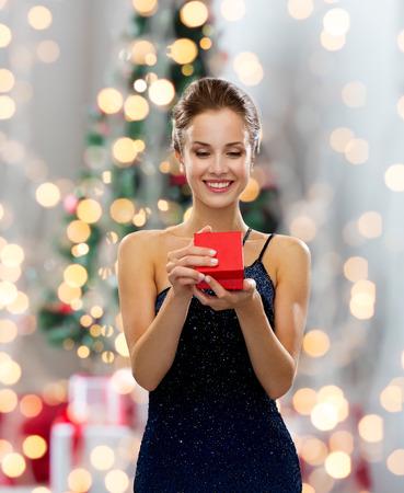 크리스마스 트리 조명 배경 위에 빨간색 선물 상자를 들고 드레스에 웃는 여자