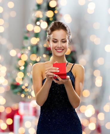 smiling woman in dress holding red gift box over christmas tree lights background Stockfoto