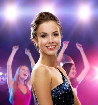 vestido de noche: mujer sonriente en traje de noche sobre fondo de discoteca Foto de archivo